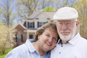 Attractive Happy Senior Couple in Front Yard of House.